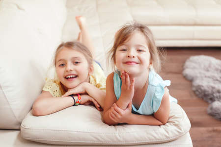 Two cute little Caucasian girls siblings playing at home. Adorable smiling children kids lying on couch together. Authentic candid lifestyle domestic life moment. Happy friends sisters relationship. Standard-Bild - 141483215