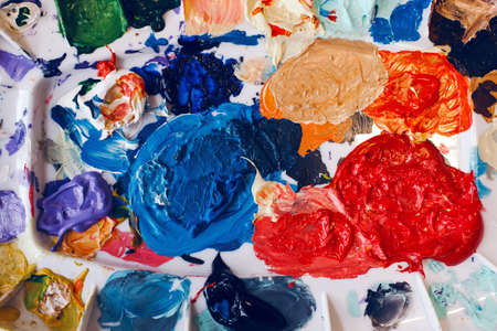 Beautiful colorful textured paints background. Paint strokes and left overs residues of paints in palette colour array on table. Colored spots and blotches stains. View from top above. Standard-Bild - 142574284