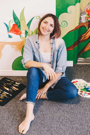 Caucasian woman artist relaxing after hand painting murals on walls indoor at apartment or studio school with acrylic paints. Creative hobby and freelance artistic work side job concept. Standard-Bild - 142574285