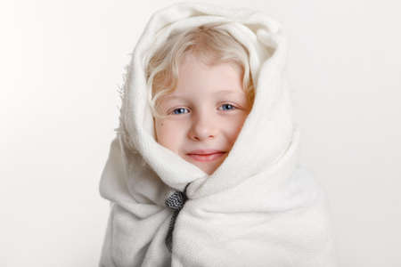 Portrait of beautiful smiling Caucasian girl wrapped in white blanket. Happy preschool child with blue eyes covered with warm woollen shawl on light background. Positive emotion face expression.