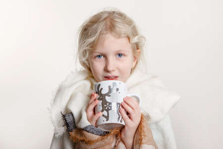 Portrait of beautiful Caucasian girl wrapped in white blanket and drinking from cup. Happy preschool child with blue eyes covered with warm woollen shawl holding winter mug. Standard-Bild - 142574295