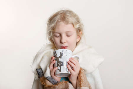 Portrait of beautiful Caucasian girl with closed eyes wrapped in white blanket and drinking from cup. Preschool child covered with warm woollen shawl holding winter mug with tea hot chocolate. Standard-Bild - 142574301
