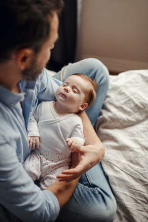Middle age Caucasian father with sleeping newborn baby girl. Parent holding rocking child daughter son in hands. Authentic lifestyle parenting fatherhood moment. Single dad family home life. Standard-Bild - 141913702