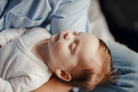 Closeup of cute sleeping newborn baby girl boy. Parent holding rocking child daughter son in hands. Authentic lifestyle parenting family life and childhood moment. Standard-Bild - 142574319