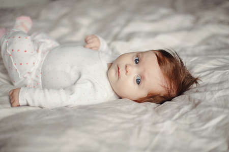 Closeup portrait of cute Caucasian newborn baby. Adorable funny child infant with blue grey eyes and red hair lying on bed looking at camera. Authentic childhood and lifestyle candid moment. Standard-Bild - 141800208