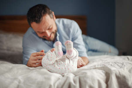 Proud Caucasian father playing with newborn baby girl. Smiling  man parent talking to child daughter son. Authentic lifestyle happy parenting fatherhood moment. Single dad family home life. Standard-Bild - 141800270