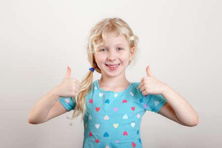 Portrait of beautiful little funny joyful blonde Caucasian girl on light background. Happy smiling preschool child kid showing like thumb fingers. Positive emotion face expression. Standard-Bild - 141913719