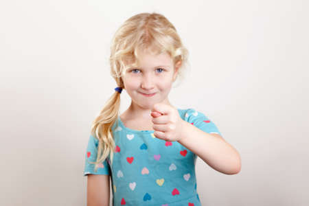 Child girl showing fig sign. Kid expressing strong negative emotion. Cute adorable blonde Caucasian preschool girl posing in studio on light background. Standard-Bild - 142574383