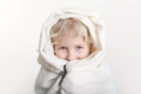 Portrait of beautiful smiling Caucasian girl wrapped in white blanket. Happy preschool child with blue eyes covered with warm woollen shawl on light background. Positive emotion face expression. Standard-Bild - 141913591