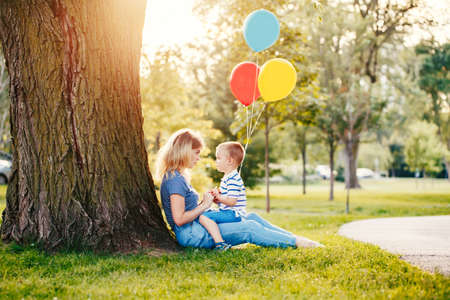 Young Caucasian mother and boy toddler son sitting on green grass together in park. Family mom and child talking communicating outdoor on summer day. Happy authentic family childhood lifestyle. Standard-Bild - 142574410