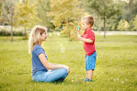 Young Caucasian mother and boy toddler son blowing soap bubbles in park. Mom and child playing having fun together outdoor on summer day. Happy authentic family childhood lifestyle. Standard-Bild - 142199109