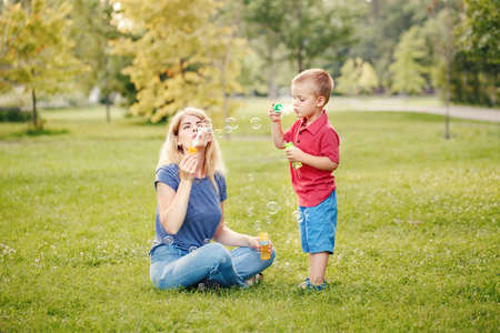 Young Caucasian mother and boy toddler son blowing soap bubbles in park. Mom and child playing having fun together outdoor on summer day. Happy authentic family childhood lifestyle. Standard-Bild - 142199095