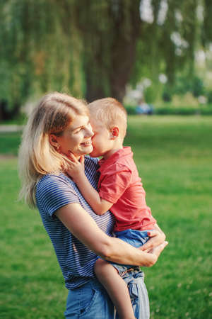 Young smiling Caucasian mother holding cuddling with boy toddler son. Laughing mom hugging embracing child outdoor in park on summer day. Happy authentic family childhood lifestyle. Standard-Bild - 142574416