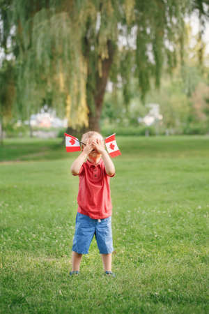Caucasian baby toddler boy standing on green grass in park outside and holding waving Canadian flag. Kid child citizen celebrating Canada Day on 1st of July. Standard-Bild - 142574423