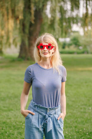 Beautiful blonde Caucasian young girl wearing canadian maple leaf sunglasses. Happy woman with funny red glasses. Citizen female celebrating Canada Day on July 1 outdoor. Standard-Bild - 142574430