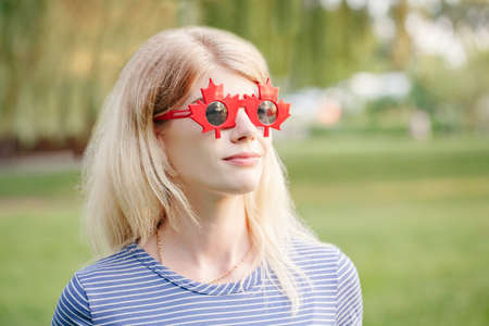 Beautiful blonde Caucasian young girl wearing canadian maple leaf sunglasses. Happy woman with funny red glasses. Citizen female celebrating Canada Day on July 1 outdoor.
