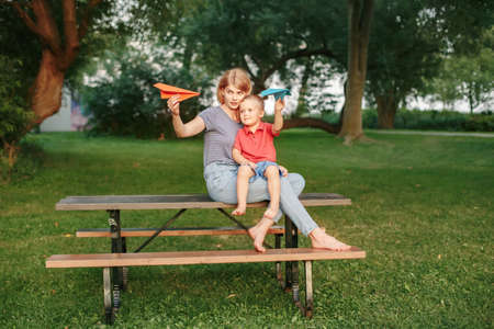 Mom and kid playing with paper air planes. Young Caucasian mother and boy toddler son sitting together outdoor on summer day. Happy family childhood lifestyle. People dreaming of future. Standard-Bild - 142574449