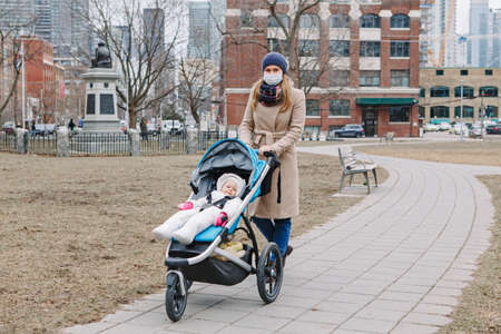Young Caucasian mother in surgical mask walking with baby outdoor in Toronto. Protective face mask precaution against new Chinese atypical pneumonia COVID-19 epidemic virus disease. Standard-Bild - 142574454