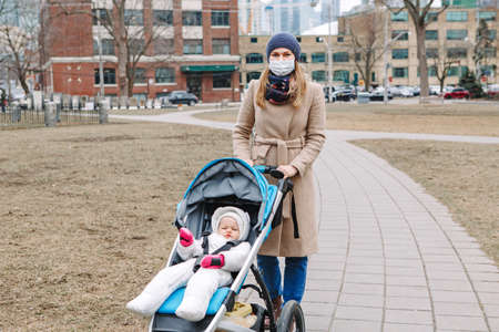 Young Caucasian mother in surgical mask walking with baby outdoor in Toronto. Protective face mask precaution against new Chinese atypical pneumonia COVID-19 epidemic virus disease. Фото со стока