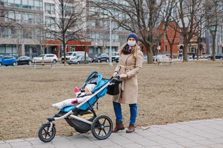 Young Caucasian mother in surgical mask walking with baby outdoor in Toronto. Protective face mask precaution against new Chinese atypical pneumonia COVID-19 epidemic virus disease. Standard-Bild - 142574500