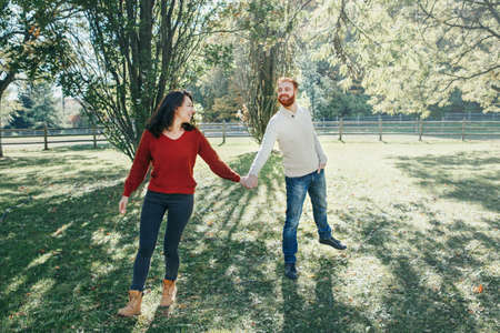 Happy couple man and woman in love walking in park outdoor. Lovely beautiful Caucasian heterosexual people dating walking on autumn fall summer day. Adult people holding hands. Standard-Bild - 142574501