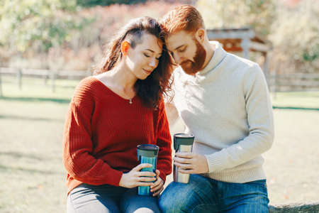 Happy couple man and woman in love sitting in park outdoor. Lovely beautiful Caucasian heterosexual people dating on autumn fall summer day. Adult people hold tea coffee drink mugs. Standard-Bild - 142574502