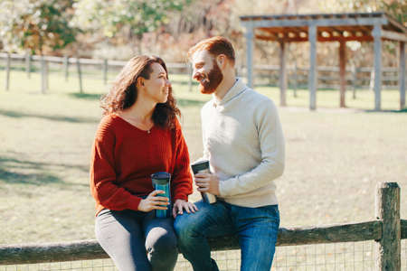 Happy couple man and woman in love sitting in park outdoor. Lovely beautiful Caucasian heterosexual people dating on autumn fall summer day. Adult people hold tea coffee drink mugs. Standard-Bild - 142574503
