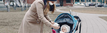 Young Caucasian mother put on surgical mask on baby. Protective face mask precaution against Chinese atypical pneumonia COVID-19 epidemic virus disease. Web banner header for website.