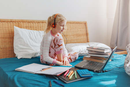 Caucasian girl child sitting in bed and learning online on laptop Internet. Virtual class lesson on video during self isolation at home. Distant remote video education. Modern school study for kids. Foto de archivo