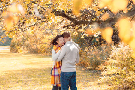 Portrait of beautiful couple man woman in love. Boyfriend and girlfriend hugging, smiling outdoor in park on bright sunny autumn fall day. Concept of togetherness and happiness.