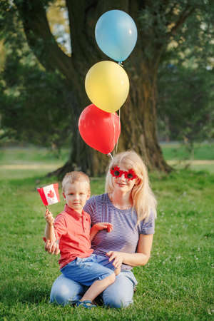Citizens family mom with kid child celebrating national Canada Day on 1st of July. Caucasian mother with baby toddler boy wearing funny maple leaf and heart sunglasses.