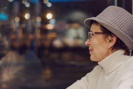 Closeup portrait of happy Caucasian old woman. Beautiful smiling mature old senior female looking away. Emotional portrait of old human enjoying life.
