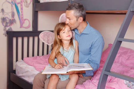 Father and daughters girl at home spending time together. Parent kissing hugging child. Family two people sitting on bed in bedroom reading book. Authentic candid lifestyle. Fathers day holiday.