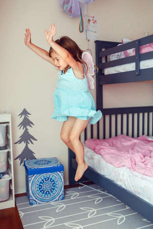 Cute Caucasian girl jumping from bed. Happy excited kid having fun at home. Adorable child playing game flying like elf or fairy. Authentic action candid lifestyle domestic life moment.