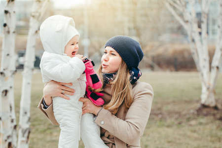 Happy smiling young Caucasian mother holding baby daughter outdoor on spring day. Family two people together outside at countryside or city. Authentic lifestyle with infant kids children.