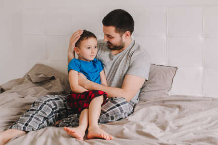 Caucasian father talking to boy son. Man parent hugs kid child on bed in bedroom at home. Authentic lifestyle real family candid moment. Happy Fathers Day holiday. Serious talk. Zdjęcie Seryjne