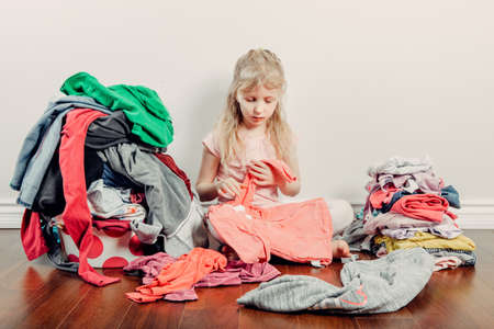 Mommy little helper. Cute Caucasian girl sorting clothes. Adorable child arranging organazing clothing. Kid with messy stack of clothes things on floor. Home chores housework for children.
