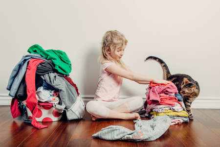 Mommy little helper. Cute Caucasian girl sorting clothes. Adorable funny child arranging organazing clothing. Kid with messy stack of clothes things on floor. Home chores housework for children. Imagens