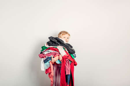 Mommy little helper. Cute Caucasian girl sorting clothes. Adorable funny child arranging organazing clothing. Kid holding messy stack pile of clothes things. Home chores housework.