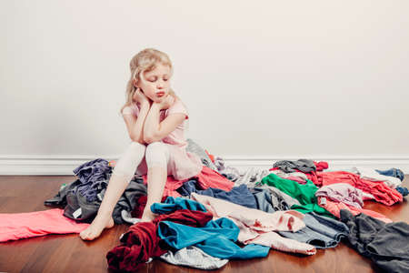 Mommy little helper. Bored Caucasian girl sorting clothes. Tired funny child arranging organazing clothing. Kid with messy stack of clothes things on floor. Home chores housework.