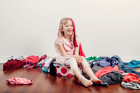 Mommy little helper. Cute Caucasian girl sorting clothes. Adorable funny child arranging organazing clothing. Kid with messy stack of clothes things on floor. Home chores housework for children.