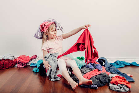 Kid playing with clothes on head. Cute Caucasian girl sorting clothes. Adorable funny child arranging organazing clothing. Messy stack of clothes things on floor. Home chores housework.