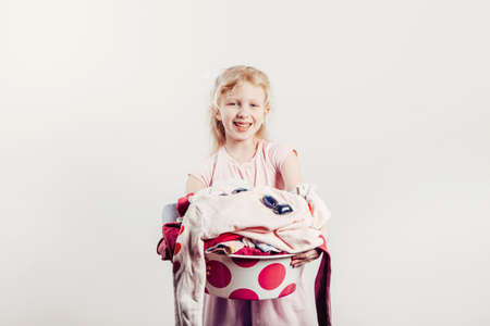 Mommy little helper. Smiling Caucasian girl child holding wash-basin with clothes and laundry detergent pods. Kid with messy stack of clothes. Home chores housework for children.