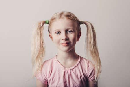 Closeup portrait of cute smiling blonde Caucasian preschool girl in pink t-shirt on light background. Child with long pig tails hair posing looking in camera. Kid expressing positive emotions.