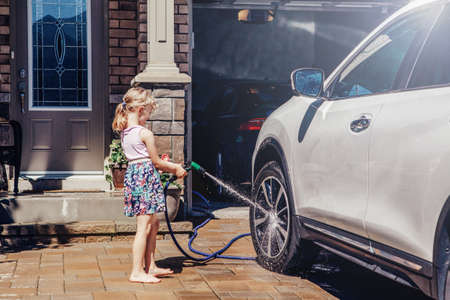 Young preschool girl washing car on driveway in front house on summer day. Kids home errands duty chores responsibilities concept. Child playing with hose spraying water. Home work lifestyle. Stockfoto