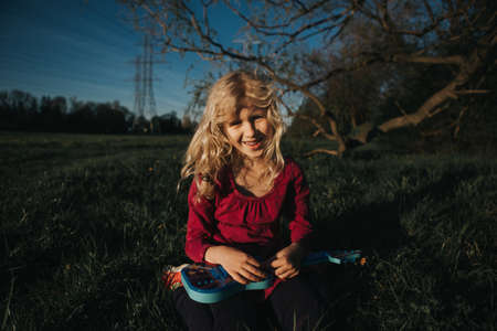Cute adorable young girl playing guitar toy outdoor. Girl pretending to be a rock music star. Adorable funny child having fun in park. Weird funny hilarious authentic candid childhood moments.