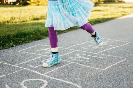Closeup of child girl playing jumping hopscotch outdoor. Funny activity game for kids on playground outside. Summer backyard street sport for children. Happy childhood lifestyle. Stock Photo