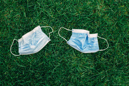 Two used sanitary masks lying on grass ground. Disposable recyclable face mask flat lay. medicine and seasonal allergy concept. View from top above overhead.