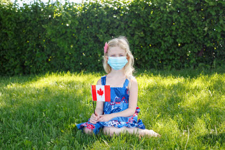 Caucasian girl in face protective mask holding waving Canadian flag outdoor. Child kid in sanitary mask on grass in park celebrating Canada Day holiday during coronavirus epidemic.