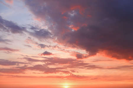 Beautiful bright colorful pink red yellow clouds on dark sky at sunset or sunrise. Evening or morning sky natural eco background. Amazing nature texture surface wallpaper.